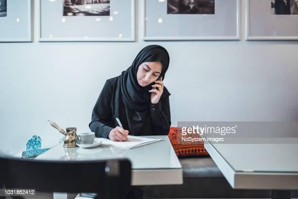 joven musulmana trabajando en café, mediante teléfono móvil - cultura árabe fotografías e imágenes de stock