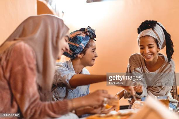 muslim young women having a lunch break together in an arab restaurant - moroccan girls stock photos and pictures