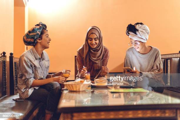 muslim young women having a lunch break together in an arab restaurant - moroccan culture stock photos and pictures