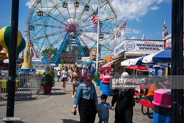 MuslimAmerican family walks through the amusement park rides area July 24 2015 at Coney Island Beach in the Brooklyn borough of New York