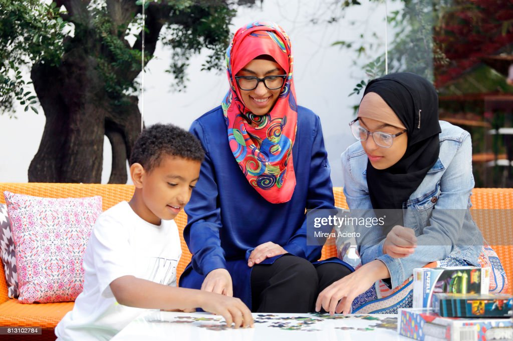 A Muslim-American mother and her two young children playing board games : Stock Photo
