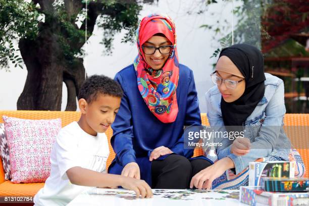 A Muslim-American mother and her two young children playing board games