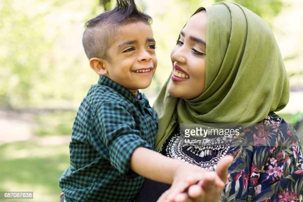#muslimgirl and son dancing in the park - muslim mother stock pictures, royalty-free photos & images