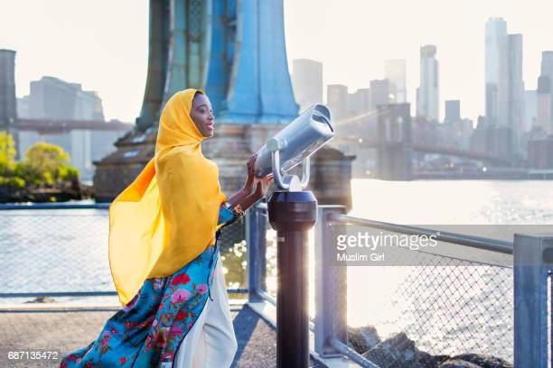#muslimgirl enjoying the view of new york city - vestido de colores fotografías e imágenes de stock