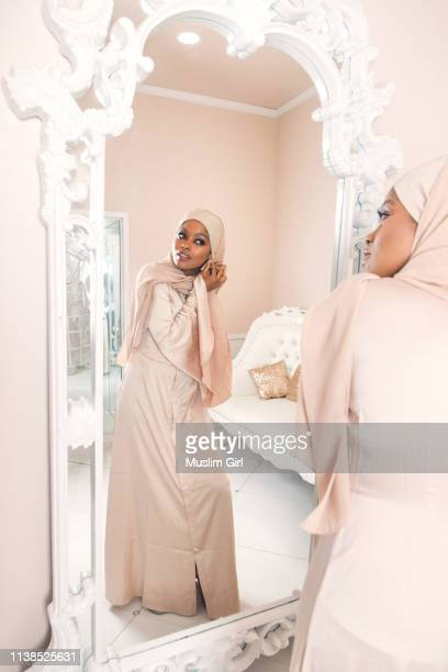 #muslimgirl fixing her earrings 2 - zurückhaltende kleidung stock-fotos und bilder