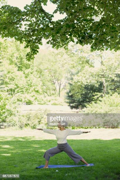 #muslimgirl practicing yoga in the park - muslimgirlcollection stock pictures, royalty-free photos & images