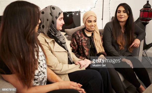 #muslimgirls iftar for ramadan - chilling on a couch - multiculturalismo foto e immagini stock