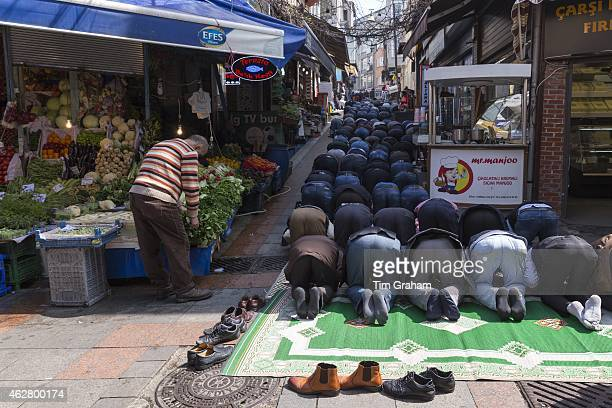 Muslims at Friday prayer on prayer mat by mosque at food and spice market Kadikoy district Asian side Istanbul East Turkey
