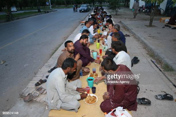 Muslims break their fasts at the iftar dinner on the first day of holy Islamic month of Ramadan in Islamabad Pakistan on May 17 2018 Traditional...