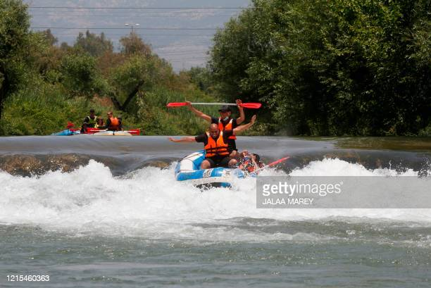 Muslims celebrate Eid alFitr holiday by rafting down the Hasbani river a major tributary of the Jordan River near the northern Israeli Kibbutz of...