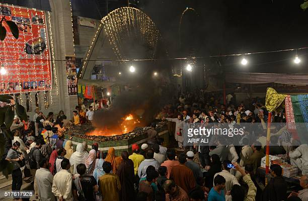 Muslims devotees gather around fire at the shrine of Sufi saint Hazrat Shah Hussain popularly known as Madhu Lal Hussain during annual festival Mela...