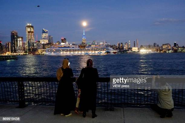 Muslims enjoy the moonrise over the Empire State Building and Manhattan skyline along the Hudson river on November 2 2017 in Hoboken NJ