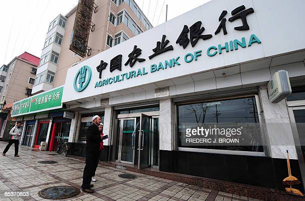 Muslims from China's Hui minority walk past a branch of Agricultural Bank of China in Xining on March 11 2009 in northwest China's Qinghai province...