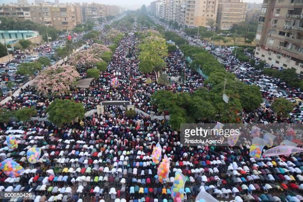 Muslims gather around the Abu Bakr alSiddiq Mosque to perform Eid alFitr prayer in Cairo Egypt on June 25 2017 Eid alFitr is a religious holiday...