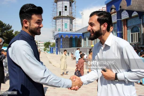 Muslims greet each other performing Eid alFitr prayer at RawzaiSharif mosque in MazariSharif Afghanistan on June 4 2019 Eid alFitr is a religious...