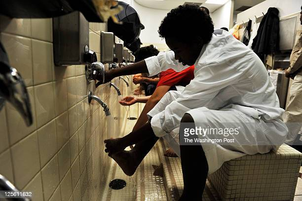 Muslims including Ahmed Ahmed wash their feet hands and face before evening Ramadan prayers at the Dar alHijrah Mosque on Aug 16 in Falls Church VA