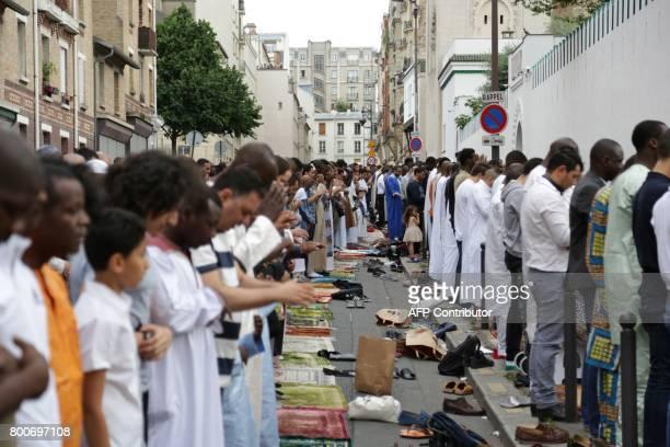 Muslims offer Eid alFitr prayers outside the Grande Mosquee de Paris in Paris on June 25 2017 Eid alFitr festival marks the end of the holy Muslim...
