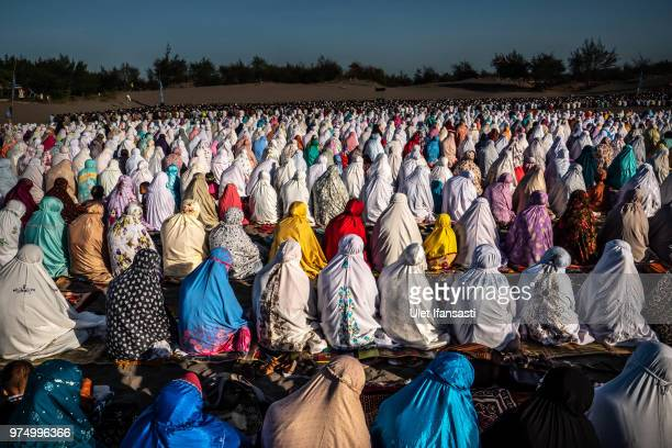 Muslims perform Eid AlFitr prayer on 'sea of sands' at Parangkusumo beach on June 15 2018 in Yogyakarta Indonesia Muslims around the world celebrate...
