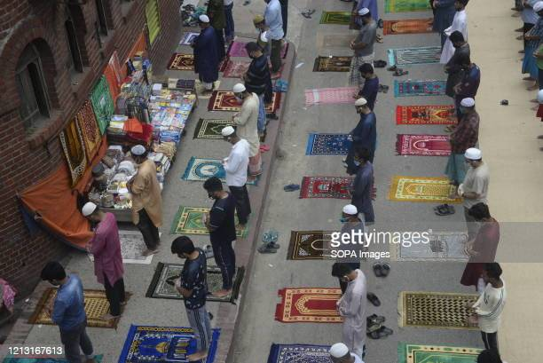 Muslims perform Jumma Namaz in an open road in front of a mosque as the mosque fills up after the Lockdown due to the Coronavirus was eased in Dhaka.