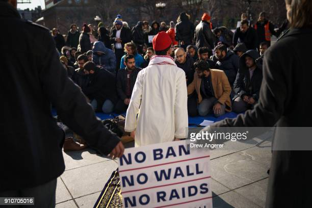 Muslims pray following a protest to the mark the one year anniversary of the Trump administration's executive order banning travel into the United...