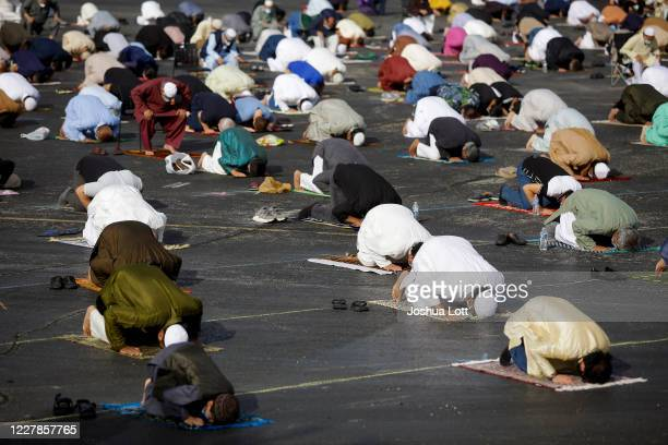 Muslims pray in the parking lot of Boomers Stadium to mark the start of Eid al-Adha on July 31, 2020 in Schaumburg, Illinois. The prayer session was...