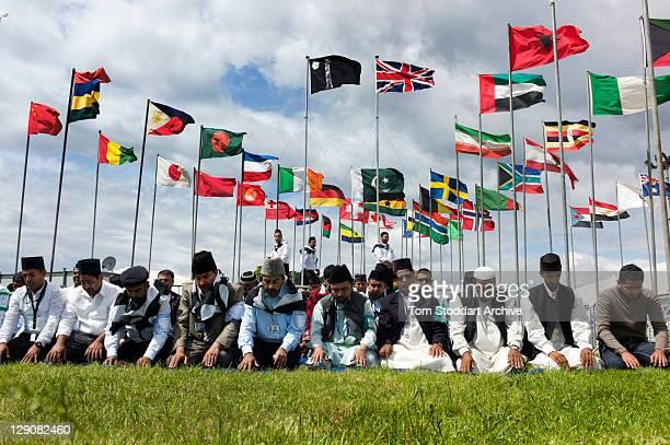 Muslims pray under flags at the 45th Jalsa Salana Ahmadiyya Annual Convention held at Oakland Farm near Alton Hampshire 24th July 2011 The Ahmadiyya...