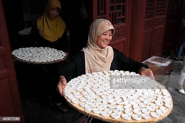 Muslims prepare food as they gather in a mosque to celebrate Eid al Fitri in Tancheng east China's Shandong province on July 29 2014 Muslims around...
