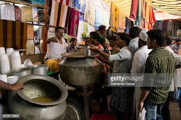 Muslims queue to buy halim on the eve of EidulFitr in the streets of central Kolkata at the end of the month of Ramadan