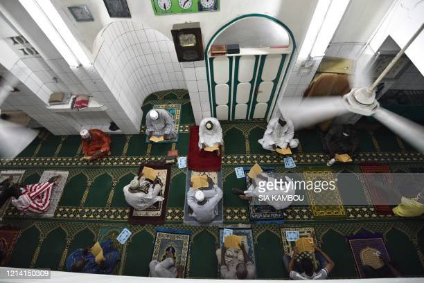 Muslims read the Koran during Laylat alQadr at the Grand Mosque of Treichville in Abidjan on May 19 after the Ivorian government has authorised the...