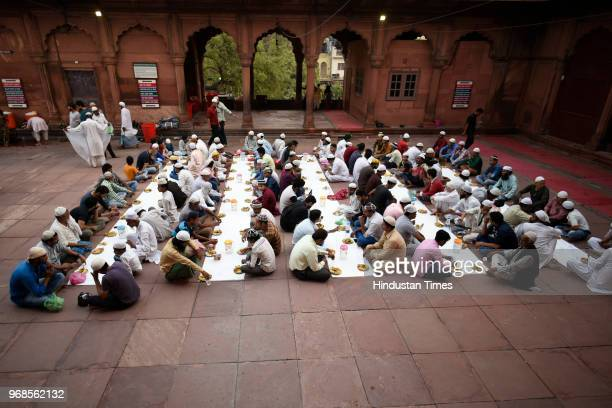 Muslims sit in queue as they wait for the announcement to be made to break the fast on the 21st day of holy fasting month of Ramadan at Jama Masjid...