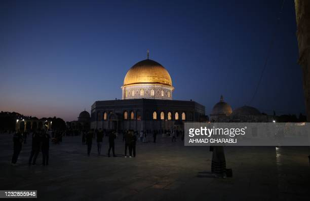 Muslims stand in front of the Dome of the Rock mosque before the morning Eid al-Fitr prayer, which marks the end of the holy fasting month of...