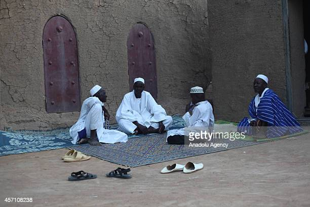 Muslims take a rest following the praying at the mosque in Djenne Mali on October 6 2014 The Great Mosque of Djenne is the largest mud brick building...