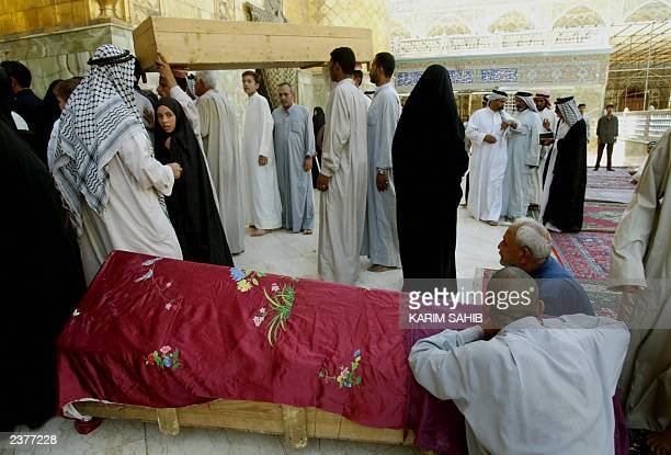 Muslims take their dead into the shrine of Imam Ali the soninlaw of Islam's prophet Mohammed 03 July 2003 in the Shiite Muslim holy city of Najaf...