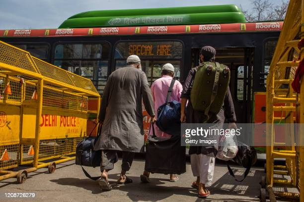 Muslims wearing protective facemasks leave an Islamic seminary to board a special service bus that will take them to quarantine facility amid...