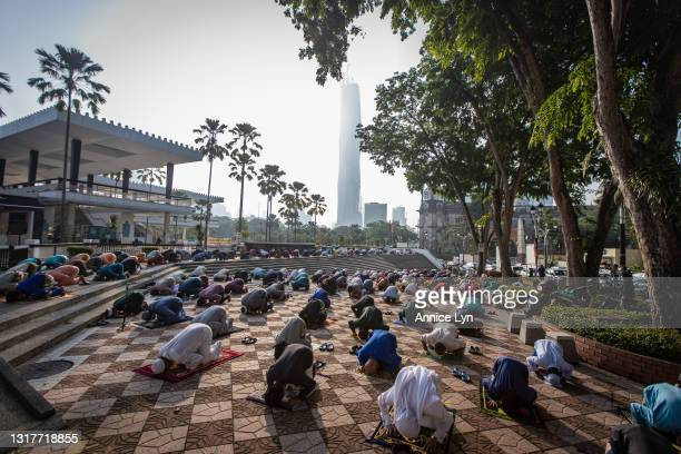 Muslims wearing protective masks pray outside the National Mosque on the first day of Eid al-Fitr on May 13, 2021 in Kuala Lumpur, Malaysia. Eid...