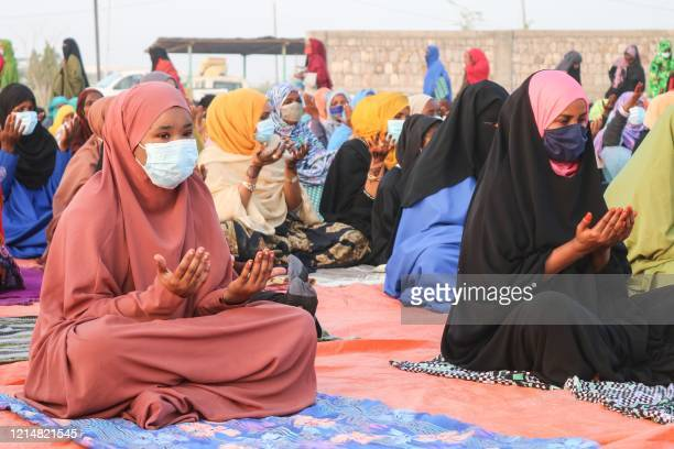 Muslims women respect social distancing as they offer Eid al-Fitr prayers marking the end of the Muslim holy month of Ramadan in Djibouti on May 24,...
