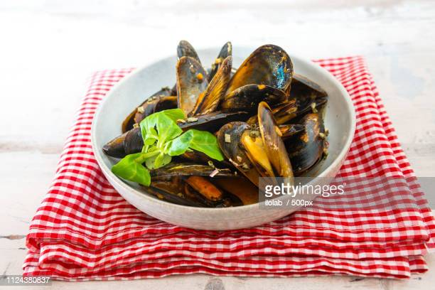 mussel with white wine sauce on table - plastic plate stock photos and pictures
