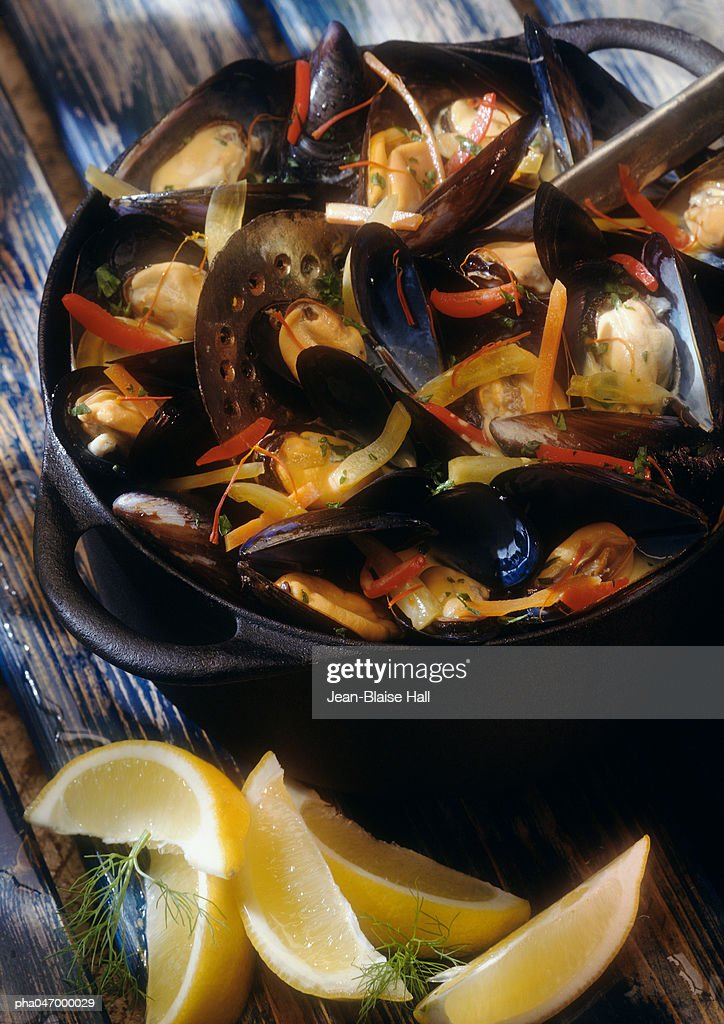 Mussels in white wine in pot with lemon wedges on the side, close-up : Stockfoto