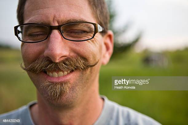 A mustached-man dons a smile in a field.
