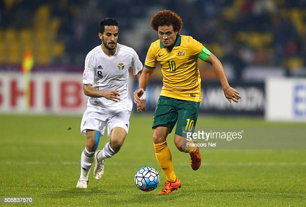 Mustafa Amini of Australia runs with the ball under pressure from Mahmoud Almardi of Jordan during the AFC U23 Championship Group D match between...