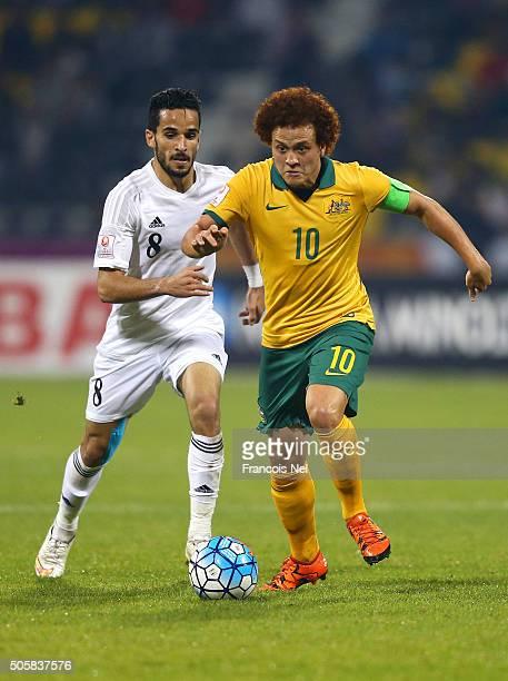 Mustafa Amini of Australia runs with the ball under pressure from Mahmoud Almardi of Jordan during the AFC U23 Championship Group D match between...