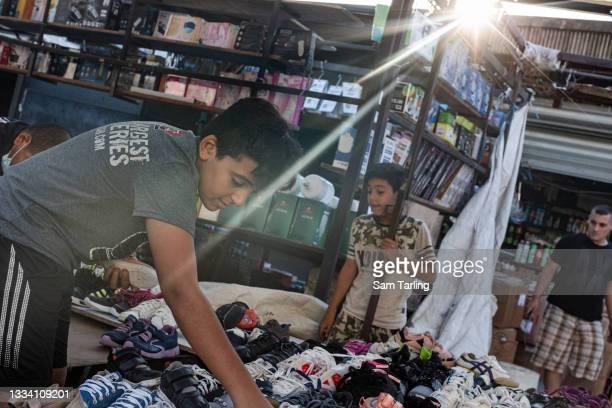 Mustafa and his brother Ahmad lay out second-hand shoes on their stall at a market in Beirut, Lebanon, on August 14, 2021. Lebanon's economic crisis...
