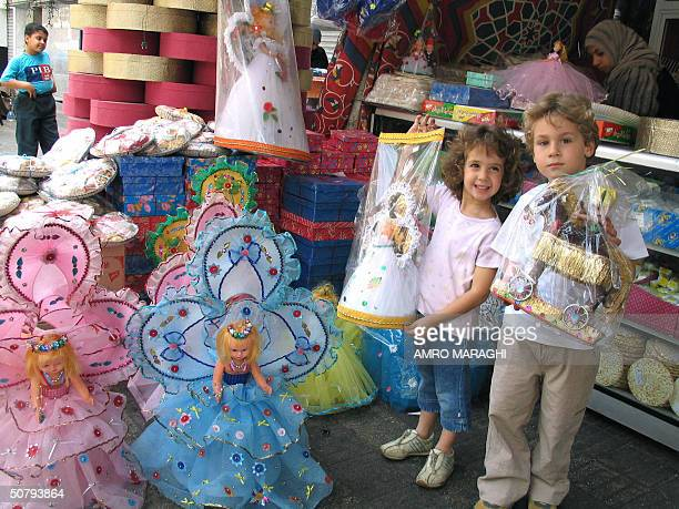 Mustafa holds his toy horse as his sister Nour shows off her AlMawlid doll during the AlMawlid celebrations in Cairo 02 May 2004 The Mawlid alNabawi...