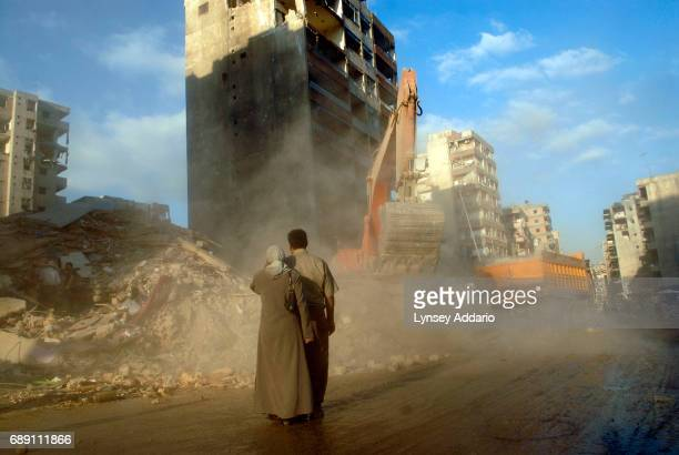 Mustafa Olwan and his wife Fatima Asadi, await the remains of their apartment in the destruction in Beirut's southern suburbs as workers clean up...