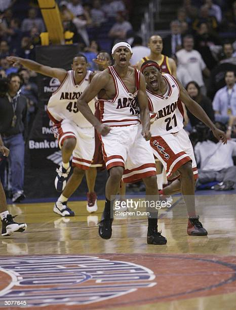 Mustafa Shakur and teammates Hassam Adams and Channing Fyre of the Arizona Wildcats celebrate Shakur's game winning threepointer against the USC...