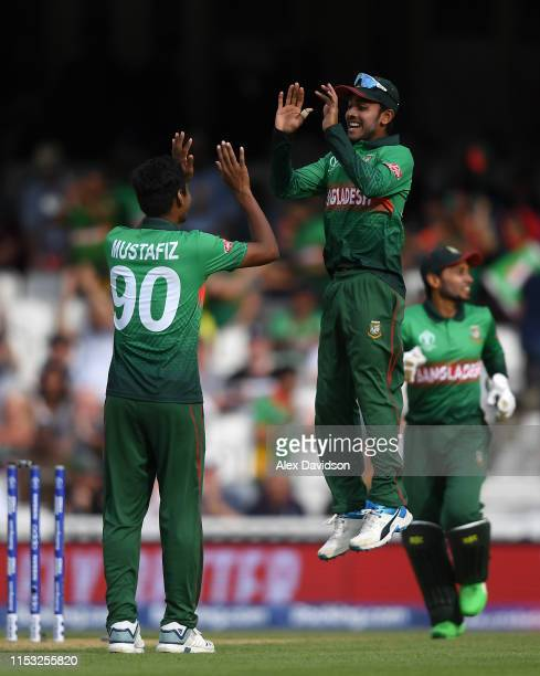 Mustafizur Rahman of Bangladesh celebrates the wicket of JP Duminy of South Africa with Mehedi Hasan of Bangladesh during the Group Stage match of...