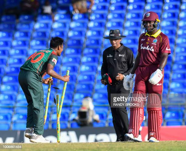 Mustafizur Rahman of Bangladesh takes the stumps from Rovman Powell of West Indies during the 3rd and final ODI match between West Indies and...