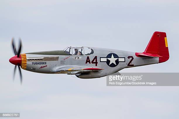 a p-51 mustang flies by at eaa airventure, oshkosh, wisconsin. - tuskegee airmen stock pictures, royalty-free photos & images