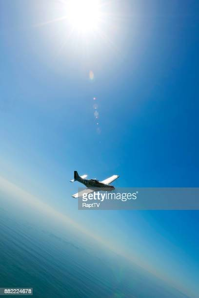 a mustang p-51 flying over the coastline and sea. - p 51 mustang stock photos and pictures