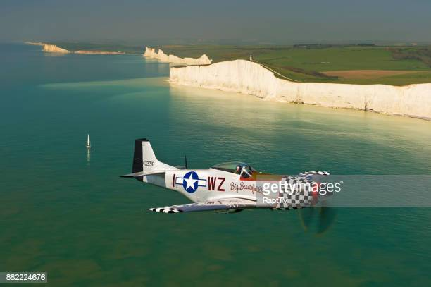 a mustang p-51 pilot flying his plane pas the white cliffs of southern england. - p 51 mustang stock photos and pictures